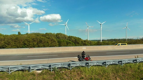 Motorcycle on the highway with a wind farm behind