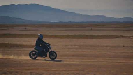 Motorcyclist crossing a desert surrounded by mountains