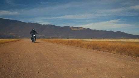 Motorcyclist crossing a dirt road in a desert