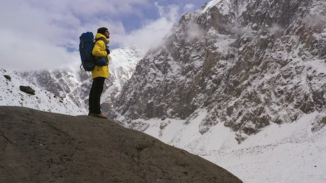 Mountaineer appreciating the view on a snowy mountain