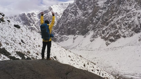 Mountaineer celebrating with raised arms in the mountains
