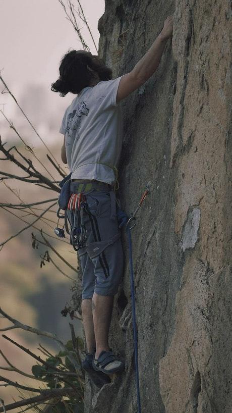Mountaineer climbing a rocky vertical mountain