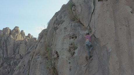 Mountaineer girl climbing a steep rocky mountain
