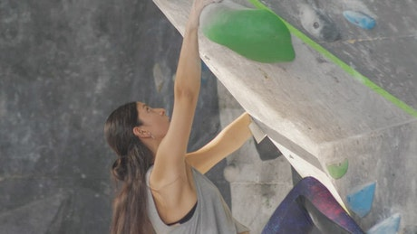 Mountaineer girl climbing a training wall