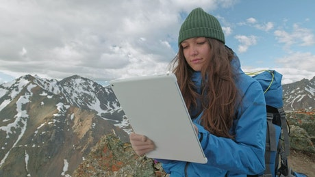 Mountaineer girl using a tablet in the mountains
