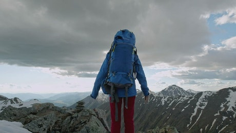 Mountaineer raising hands on top of a mountain