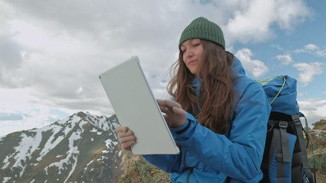 Mountaineer using a tablet on a mountain