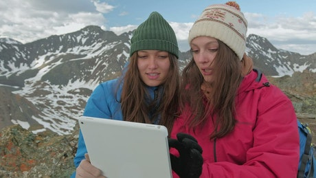Mountaineers using a tablet on top of a snowy mountain