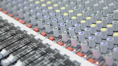 Moving faders and knobs on a sound console