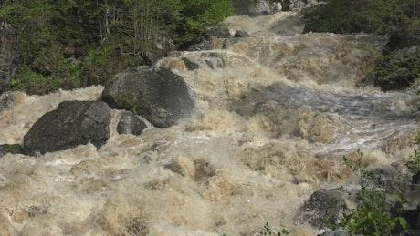 Muddy river rapids and rocks