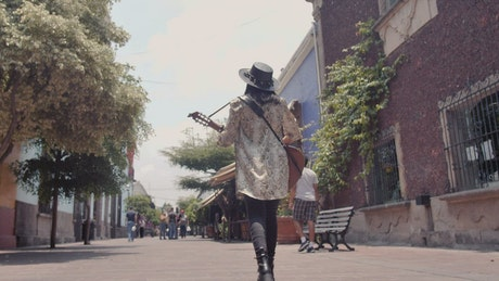 Mujer caminando por una calle colonial mientras toca su guitarra