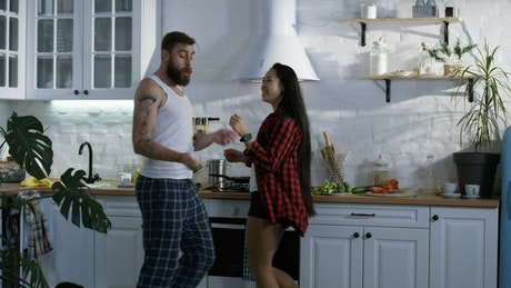 Multi racial couple dancing in the kitchen