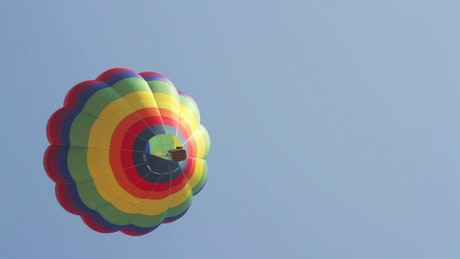 Multicolored hot air balloon is seen from below