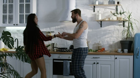 Multiracial couple dancing in the kitchen