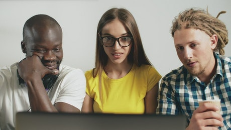 Multiracial friends react in surprise while watching video