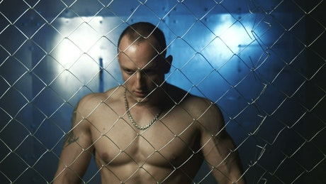 Muscular man behind a wire fence