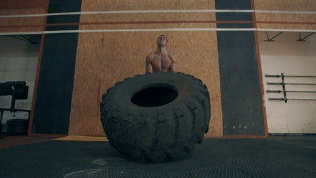Muscular man doing CrossFit exercises with tire