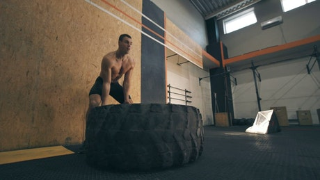 Muscular man doing CrossFit with a big tire