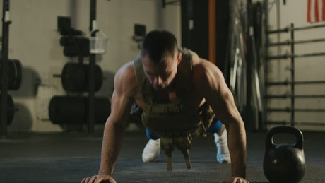 Muscular man doing push-ups in the gym