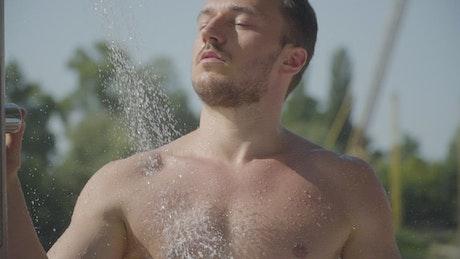 Muscular man in outdoor beach shower