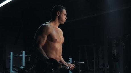 Muscular man lifting a barbell in a dark gym
