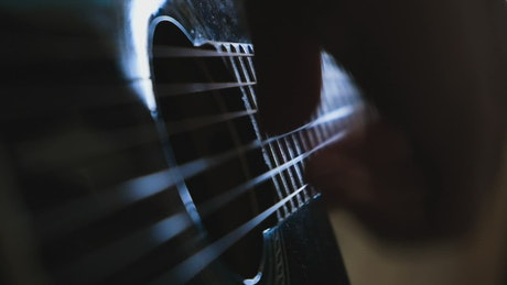 Musician playing a guitar indoors