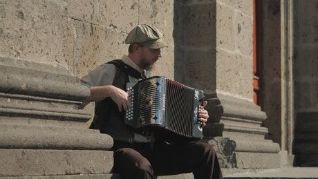 Musician playing accordion in front of a concrete building