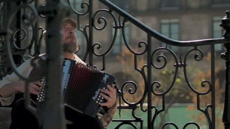 Musician playing accordion on steps
