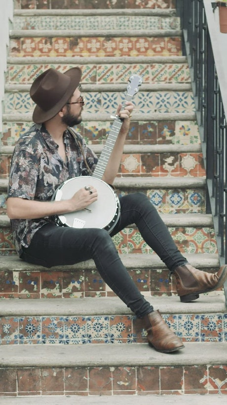 Musician sitting on an old ladder playing his banjo