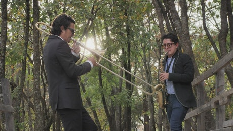 Musicians playing wind instruments in the forest
