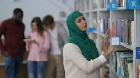 Muslim student browsing a library