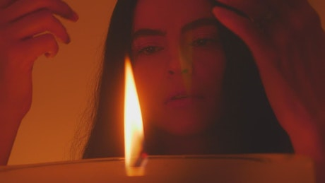 Mysterious woman appreciating the flame of a candle