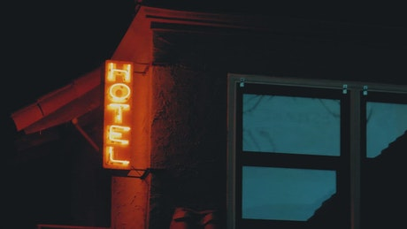 Neon light of a hotel flickering in the dark