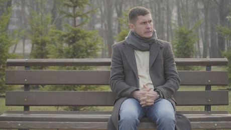 Nervous man sits on park bench waiting