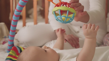 Newborn baby plays with a toy