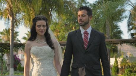 Newlyweds walking through a garden