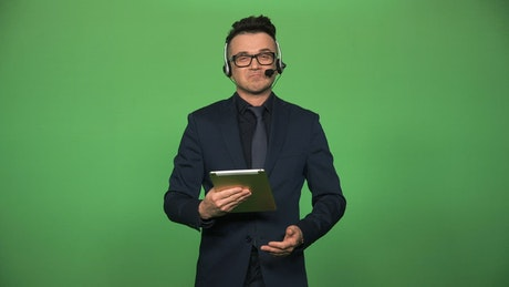 Newscaster with tablet and headset speaking