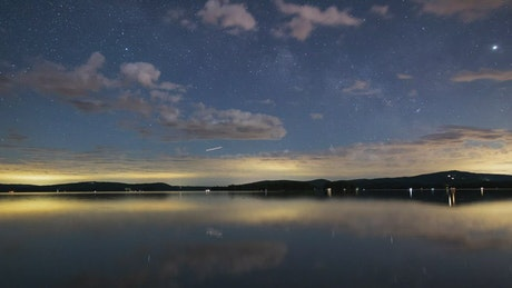 Night sky with stars at a calm lake, time lapse