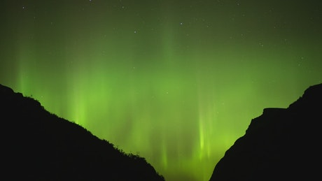 Northern Lights behind two mountains