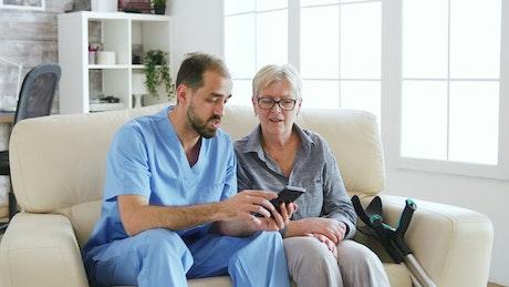 Nurse helps woman use app on mobile phone