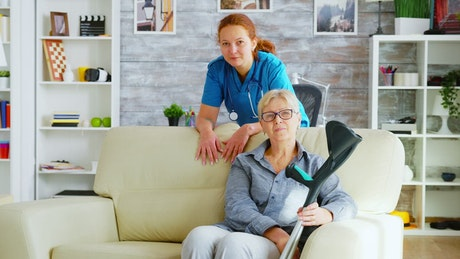 Nurse stands with elderly patient sitting on sofa