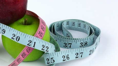 Nutritionist measuring tapes and apples