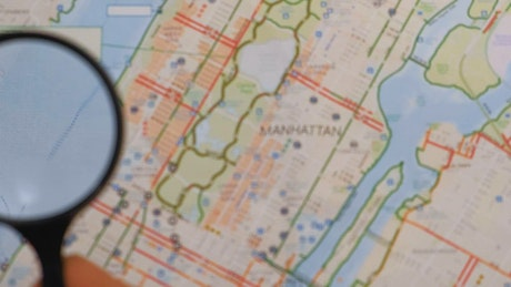 Observing with a magnifying glass on a map of Manhattan