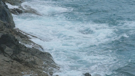 Ocean waves crashing at the cliff