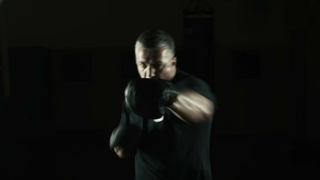 Old boxer training in a dark room