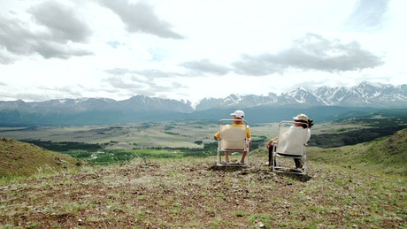 Old couple looking at the horizon on a hill