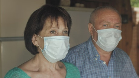 Old couple taking off their masks at home