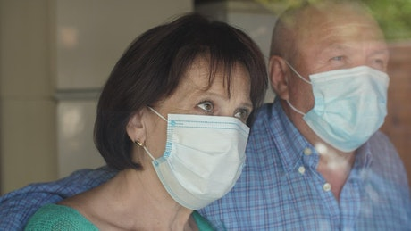 Old couple with face masks, portrait