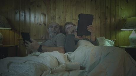 Old couple with tablets in the bedroom