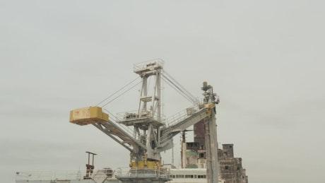 Old crane loading ships on a coast